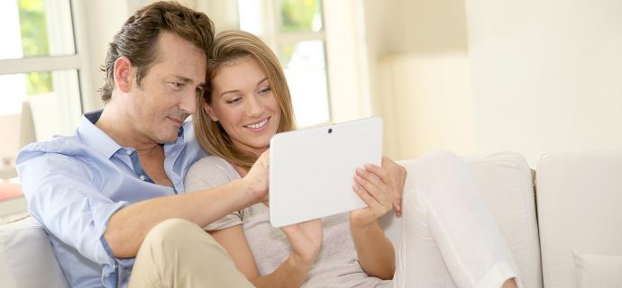 Couple in sofa websurfing on internet